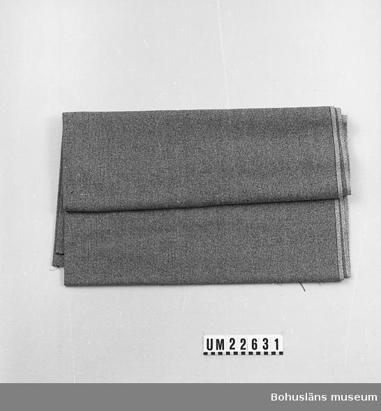 594 Landskap BOHUSLÄN  Fabrikssytt ylletyg. Vävt av svart och gråvitt garn. Två vita trådar i stadkanten.  UMFF 117:1