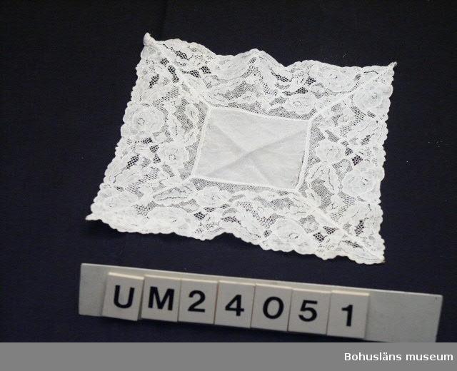 Näsduk med bred spets. Använd vid konfirmation i Stenkyrka kyrka 1956. Bristningar i infällda mittpartiet längs 2 motsatta kanter. Sammanhör med klänning UM 24050.