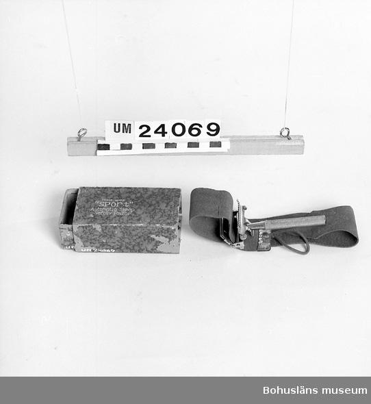 """594 Landskap BOHUSLÄN  Mått ovan anger låda. Förkromad stålhållare med läderstrigel. På strigeln inpressat: """"SAFETY RAZER STROP ZET, MALER BRAND LTD"""". Papplåda med brun-svart melerat papper. Silvertext på ovansidan: """"Trade Mark SPORT. Automatic Strop Safety Razer"""". Sönder i en kant. Föremål från Brorssons Damfrisering i Kungshamn, se UM023941."""