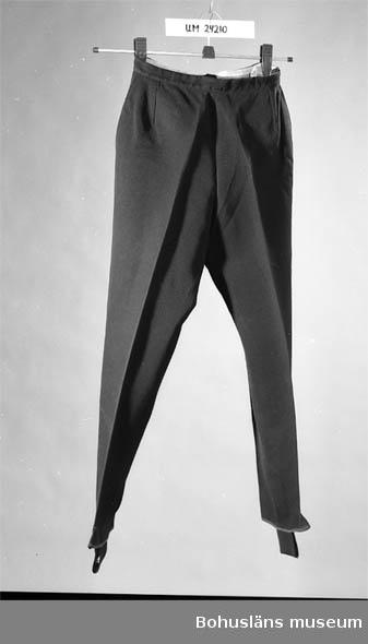 Svarta elastabyxor (C 175). Hälla under foten. Dragkedja och knapp i  ena sidan. Tvättinstruktioner på en lapp i linningen. Byxorna tillsammans med en tröja (UM024211) samt en orangefärgad anorak med dragkedja fram och  kapuschong med svart pälskant + promenadskor, användes som skolkläder när givaren (f. 1944) gick i skola i Lysekil.