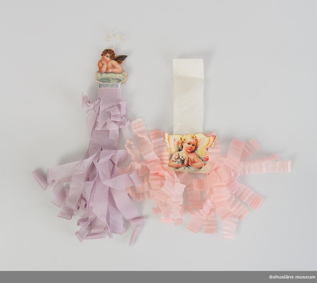 """Smällkaramell. 1) Röd/vit """"12-öres platta"""" med pajasbokmärke. Veckad frans i båda ändarna.  2) Rosa/vit """"12-öres platta"""" med flicka (bokmärke). Veckad frans i båda ändarna. 3) Rosa med guldpappersspiral """"12-öres runda"""". Veckad frans i båda ändarna.  4) """"Murvel"""" mellanröd/vit med guldpapperskjol, tillverkad med specialverktyg. Veckad frans i båda ändarna. 5) """"Rosor/chrysantemum"""" röd/vit med bokmärke motiv: ängel som håller en fiol. """"Krusat"""" i båda ändarna. 6) """"Rosor/chrysantemum"""" rosa med bokmärke motiv: violbukett. Krusade delen i båda ändarna tillverkad med specialverktyg. 7) """"Fågel"""" rosa/vit med bokmärke: motiv ängel med liljekvist. Upphängningsanordning av silkepapper. Veckad frans i nedre delen. 8) """"Ängel"""" ljus blåröd. Med dubbelmärke motiv: ängel Rafael. Rullad frans i nedre delen.  Vit lite glansig tråd som upphängningsanordning på alla utom en som har silkepappershänge istället. Tillverkade för museets julgran år 1990 efter Augusta Lundbergs modeller från 1900-talets början. Lundberg var karamellkokerska i Uddevalla."""