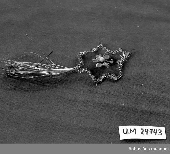 471 Tillverkningstid 1920-40 ? 594 Landskap BOHUSLÄN  Metalltråd böjd till en blomsterliknande form. Klädd med tunna metall-  pappersremsor. Inuti är det en blomma av grönt metallpapper. Nedtill hänger det raka metallpapperremsor.  Givarens mamma född Augustsson (1898 - 1978).