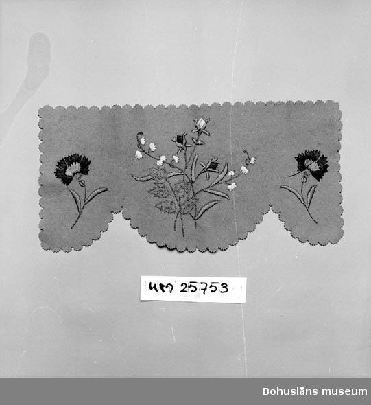 Grön boj, klippa, kanter, nedtill tre stora halvcirklar. Hela kanter runt om med små taggiga halvcirklar. Broderade blommotiv i rött, vitt, rosa och grönt i schattersöm, plattsöm och kedjesöm. Användes vid högtidliga tillfällen. Se UM025750 - UM025753. Personuppgifter se UM025730 och UM025739.