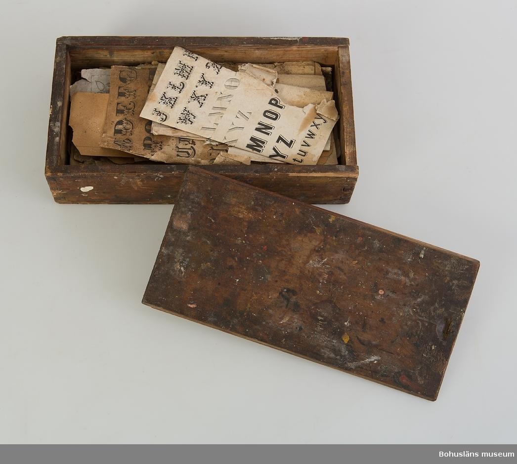Rektangulär sinkad låda med skjutlock. På en av lockets kortsidor finns en urgröpning att sätta fingret och dra i. Har varit mörkbetsad. På utsidan är det en mängd olika färgfläckar. Inuti lådas nförvaras förlagor till schablonbokstäver för dekorationsmåleri. Övriga upplysningar se UM025763