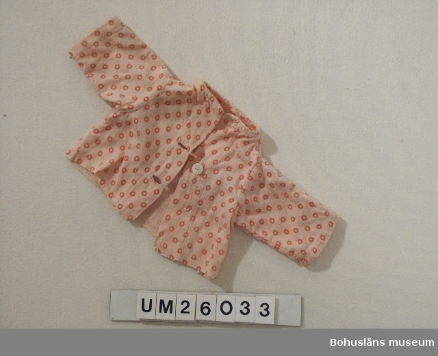 """Av rosa flanell med mörkare rosa ringar. Ståndkrage. Knäppt med två naturfärgade benknappar varav den nedre saknas.  Hör till dockan """"Kerstin"""" UM026024 och hennes utrustning. Personuppgifter se UM026024"""