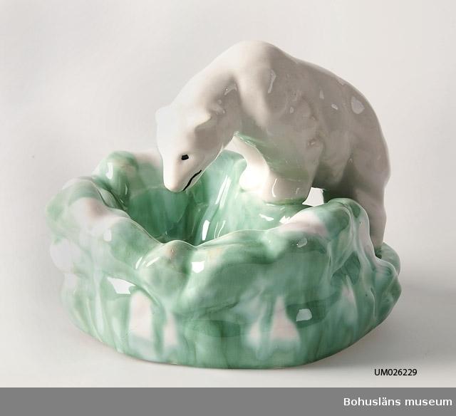 Vitglaserad isbjörn med svarta ögon och svart sträck som markerar mun. Placerad på klippliknande formation glaserad med vit-grönflammig färg. Har varit signerad med fastklistrad pappersetikett från SYCO, som har försvunnit. Av givaren inköpt 1997 i antikhandel varför proveniens saknas.