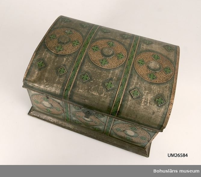 Fyrkantig låda med välvt lock. Metallen är präglad och har tryck i guld, svart och grönt bl.a. franska liljor. Utformningen är gjord för att efterlikna en kista. I lådan har förvarats de föremål som använts vid framställning av patroner till hagelgevär UM025574. Se UM026575 - UM025782