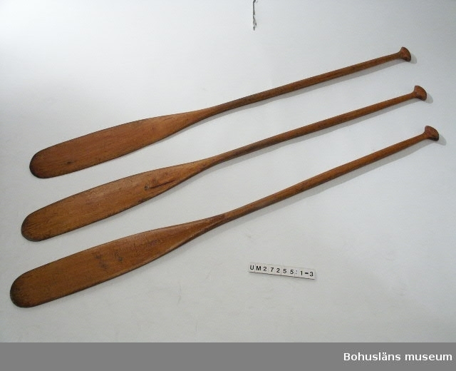 Längd forts.: Avser UM27255:1 och UM27255:2, UM27255:3 L: 1659 mm,  Bredd avser bladbredd, diam. avser skaftet.  Tre i princip likadana originalpaddlar av trä till  Macfiekanoten.  Enkelpaddel med svagt konvext blad, bladlängd ca 72 cm, största tjocklek 9 mm.  Skaft med oval genomskärning, mot bladet bredare (16 mm) mot greppet smalare, (12 mm), största bredd  mitten (19 mm).  Grepp i tillplattad knoppformad modell, största bredd 67 mm, tjockl.15 mm. Tillverkade av rödbok och fernissade eller lackade.     UM27255:3 har en spricka i bladet.  För uppgifter om kanoten, tillverkning och ägare,  se UM27254.