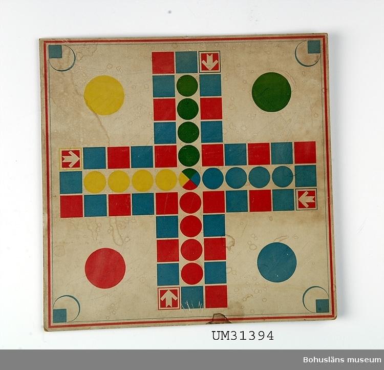"""Ett Fia-spel med spelpjäser. Kraftig kartong med tryck på ena sidan.  Spelplan med blå,  gula och röda rundlar, i mitten med texten """"MÅL"""". Nere till vänster tryckt LITO RYSTEDT GÖTEBORG På basidan tryckta spelregler inom ram: SPELREGLER FÖR FIA = SPELET I spelet kunna två toill fyra personer deltaga. Etc. Till spelet hör koniska spelpjäser, """"toppar"""" av svarvat trä och två tärningar av trä, se UM31393:2.  Föremålet har använts av familjen Abrahamson i deras sommarstuga i Sundsandvik, byggd 1939. För ytterligare upplysningar om förvärvet, se UM031385."""