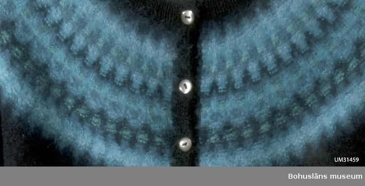 """Stickad kofta med långa ärmar. Slätstickad i svart med rundstickat okmönster på axelpartiet. Mönstret i slät- och avigstickning i angoraull med glidningar ton i ton i flera olika nyanser av blått, turkos och grönt.  Nederkant dubbelvikt längs ett avigstickat varv och monterad med stygn mot insidan, ribbstickade ärmmuddar och ribbstickad halskant.  Tio originalknappar av pärlemor. Knappslån på baksidan förstärkt med ett påsytt svart ripsband för att passformen ska hålla sig bättre. Bohus Sticknings originaletikett i nacken: Bohus Stickning Handknitted in Sweden All wool Mönstret heter """"Ägget"""" och har tillverkats i olika färgställningar.  Mönstret är komponerat av Kerstin Olson på 1960-talet.    Givaren har fått jumpern av sin mor i USA. Den är ursprungligen inköpt och använd av givarens faster, också från USA.  Jumpern är inköpt i butiken på ett förstaklass-hotell i Göteborg sommaren 1967. På samma ställe inköpte givarens föräldrar en Bohus stickning-inspirerad kofta i ljusblå ull med okmönster. Denna jumper ingick också i gåvan och är intagen som pedagogiskt material.       Litt: Häglund, U. med bidrag av Ingrid Mesterton. Bohus Stickning. Bohusläns museums förlag 1999, s. 28. Keele, W. Poems of Color. Knitting in the Bohus Tradition. And the women who drove this Swedish cottage industry. Interweave press 1995, s. 38."""