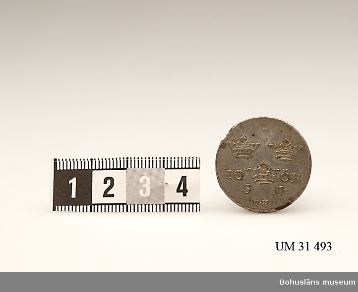 10 öre SM, 1745. [silvermynt]. Mynt  präglat under Fredrik I:s regeringstid.  Åtsida: IN DEO SPES MEA [I Gud mitt hopp] Frånsida: Tre kronor med texten 10 ÖR. S M. 10 öre SM kallades för dubbel pjäs och värdet var officiellt 12 öre trots valörbeteckningen. Kallades även för tolvstyver.  Fredrik I , 1676 -1751, kung av Sverige 1720–1751. Gift med Ulrika Eleonora d.y., (1688-1741), regerande drottning av Sverige 1719–20, syster till  Karl XII.  Förvärvsdatum okänt.  Uppgifter hämtade från Riksbankens hemsida och hemsidan Tonys mynt, Internet 2010.