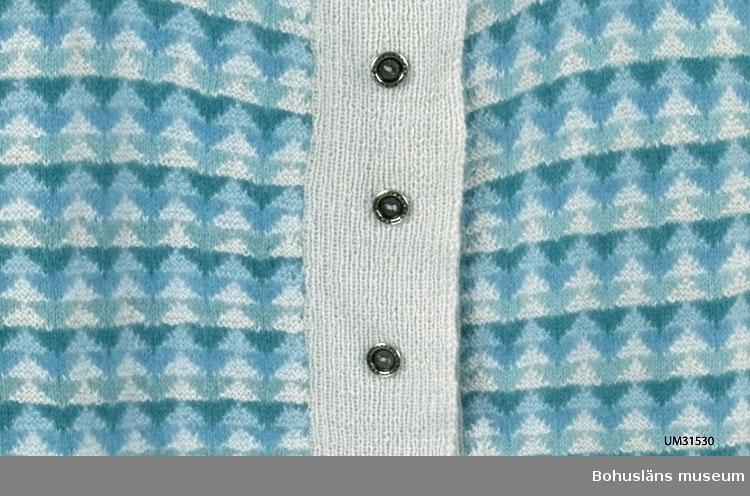 Stickad kofta med långa ärmar. Slätstickad i ljusblått med mönstrade framstycken. Mönstret i slät- och avigstickning i angoraull med glidningar ton i ton i sex olika nyanser av blått och turkos i ett upprepat mosaikmönster. Ribbstickad halskant och  ärmmuddar, bred, ej invikt ribbstickad knappslå samt  ribbstickad resår nertill som är helt invikt.  Åtta tennliknande knappar, ej Bohus Sticknings originalknappar. Saknar Bohus Sticknings etikett i nacken.