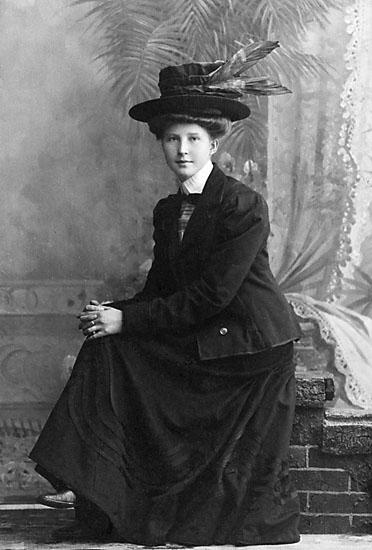 """Stämpel på framsidan: """"Falk, Karlshamn, Filial: Hoby."""" Inpräglar på fotot: """"1908."""""""
