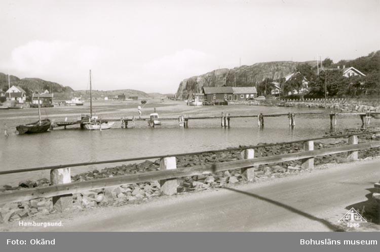 """Tryckt text på kortet: """"HAMBURGSUND"""". Noterat på kortet: HAMBURGSUND KVILLE 20 Juli 1955"""". """"UTSIKT N. GENOM SUNDET TILL V. HOMBURGÖ""""."""