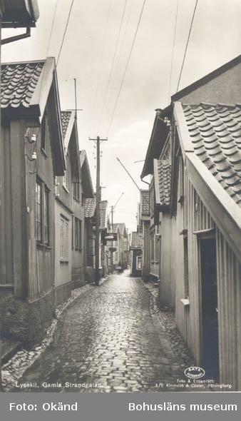 """Tryckt text på kortet: """"Lysekil. Gamla Strandgatan."""" """"Foto & Ensamrätt: A/B Almqvist & Cöster Hälsingborg."""" """"Förlag: Torsten Bergqvist, Tobak & Pappershandel, Lysekil."""""""