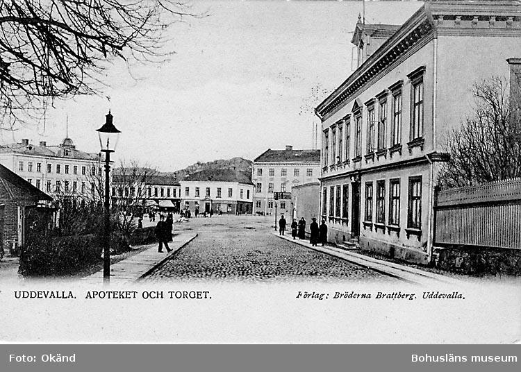 """Tryckt text på vykortets framsida:""""Uddevalla Apoteket och Torget"""".  ::"""