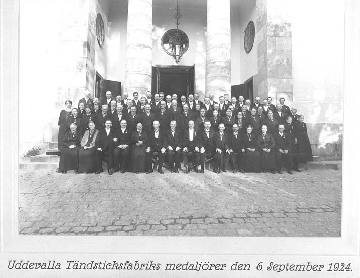 """Text till kortet: """"Tändsticksfabriken firar 50 års jubileum. Uddevalla Tändsticksfabriks medaljörer den 6 september 1924 på trappan till Uddevalla kyrka."""""""