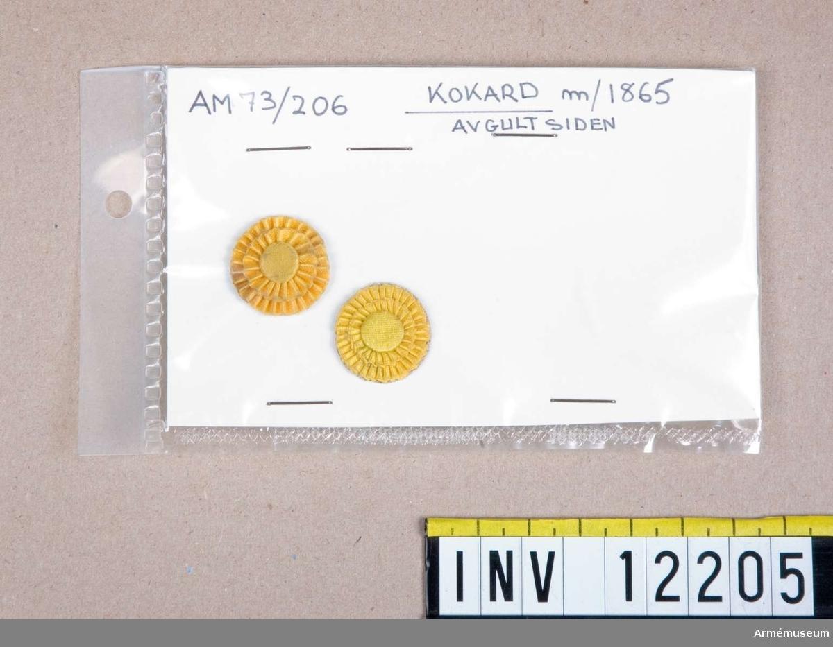 Grupp C I.  Kokard m/1865 av gult siden. 2 delar.  Gåva från kapten A de Roubetz.