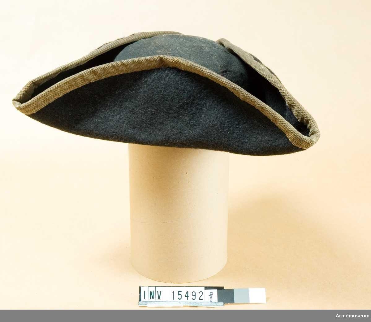 Grupp C I. Trekantigt uppviken hatt av svart filt med vitt ylleband i kanten. Köp 1884.