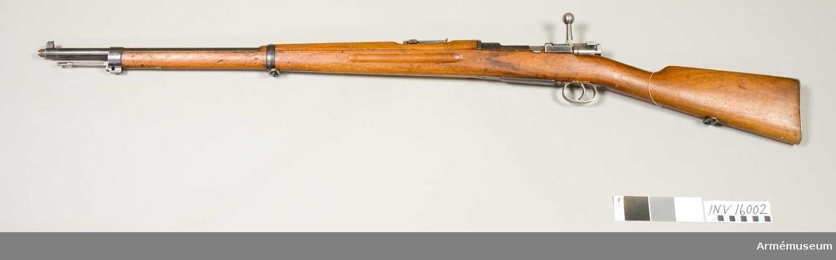 """Gevär m/1896 B. System Mauser.Tillv.nr 2820 år 1900. Märkbricka av mässing på kolvens högra sida. Märkt """"O:G."""" Mekanismens handtag är rakt. Mynningsgänga för lösskjutningsanordning. Gängskydd saknas. Riktmedel: ramsikte graderat för avstånd 300-600 m."""