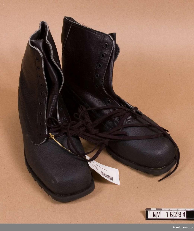 Med foten av gummi och med skaften av läder. Snörning. Gummisulor med namnet på tillverkare TRETORN 1980 27. Arbetsmodell för M 7336-115000-9, 1983-02-17.