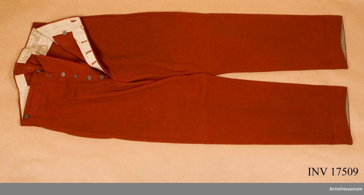 """Grupp C I. Byxor (pantalon d'ordonanance) av rött kläde. De har två sidofickor och en ficka på framsidan (för klocka). Knapparna är alla av järn med påskriften: """"Equipements militaires"""" - 5 st för sprund, 4 st för hängslen. Fodret är av vitt tyg med många stämplar: 1) """"Ateljers militaire. Bigetre 3.99.e4"""" (rund stämpel på baksidan); 2) """"B-4"""" """"89-90"""" - troligen storlek; 3) """"C.P. Commission de réception - 31/7. 1899""""; 4) W. Arel"""" """"AR"""" """"G.P.W."""". På byxbenens nedre del (baksidan) finns ett 7 cm brett uppslag av grov lärft. Litteratur: Enligt Handbuch der Uniformkunde, Prof Rich. Knötel, Hamburg  1937 sid. 166: Efter år 1829 bar franska infanteriet röda byxor. Dessa var i bruk till år 1915. Sid. 161: De röda  byxorna kan användas dels instoppade i de vita linnedamaskerna och dels tagna utanpå dessa. Arméen Album II. Die Französische Armée. Verlag von M. Ruhl Leipzig 1937, sid 20 Infanterie. Byxor av krapprött kläde. Bilaga. Sid. 2 Infanterisoldat i röda byxor. Collection complete des tracés de coupe des Effets d'Habittement. Ministere de la Guerre, 1845-47. Plansch 5 """"Byxor"""" Infanterie de ligne: ritningar och mått på byxor."""
