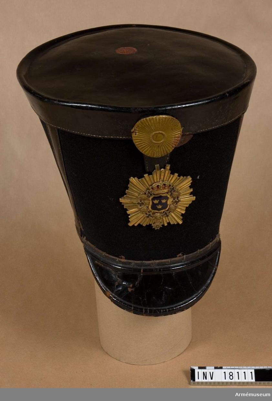 """Grupp C I. Huvudbonad, manskap, andra livgardet. Huvudbonad av filt med det s k Göta vapen utbytt 1824 mot Svea vapen """"Tre kronor"""". 1812-1837."""