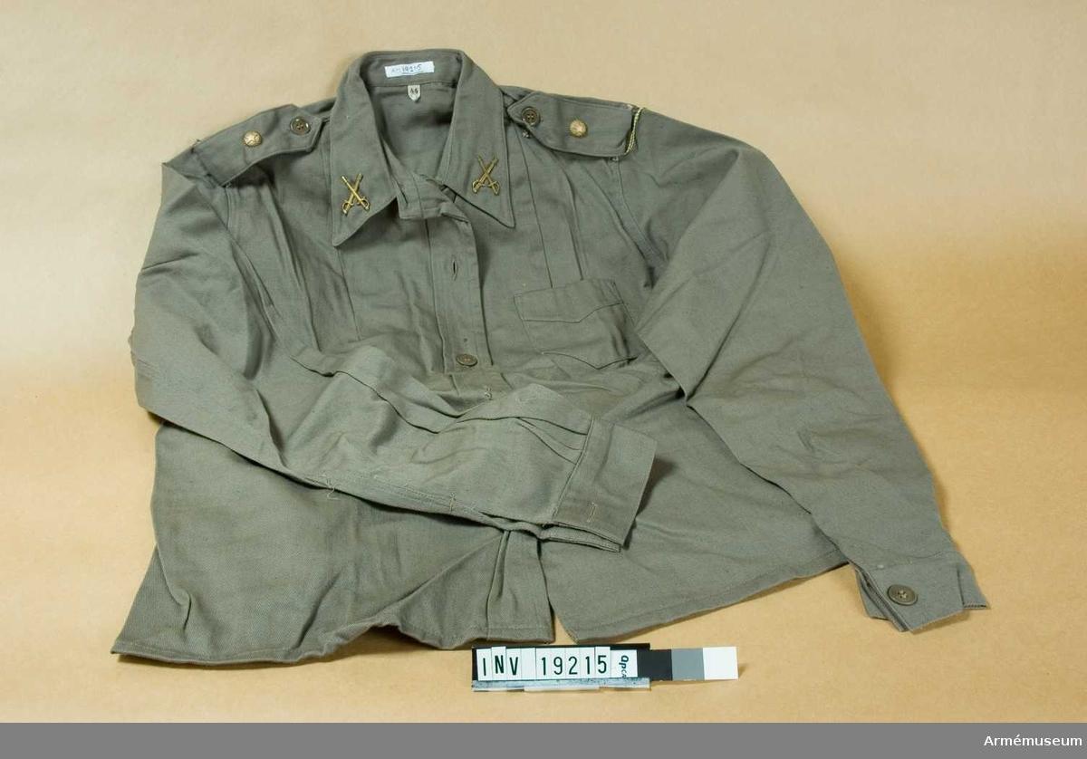 """Av gråbrungrön bomullskypert (diagonal) med fast krage i snibb. Knäppslå med fem knappar framtill. Lösknäppbara axelklaffar. Fastknäpps med knapp och dras genom två hällor över axelsömmen. Har en stjärnknapp m/1939 =sergeant. En bröstficka på vänster sida. Isydd ärm med fast manschett och knäppt med en knapp. Ryggen är något figursydd. Storlek 44. Märkt """"Cegecé"""". På kragsnibbarna truppslagstecken för kavalleri. Har tillhört mobiliseringsutrustning vid museet för Gun Adler."""