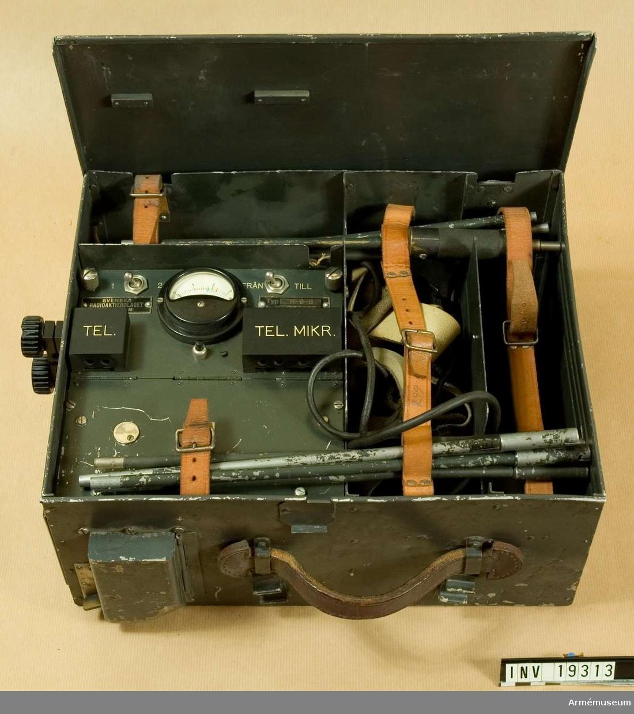 """Radiostation m/1940. ½ Watts. (Typ H-9-B). Bärbar.  Tillverkningsnummer: 007402.  Märkt: ½ W Br Nr. 299. Består av 10 delar. 1 st radiostation. 6 st antennstavar av aluminium. 2 st antennstavar med fäste av gummi. 1 st hörtelefon med sele och mikrofon med en """"tratt"""". Radiostationen ej komplett, delar saknas. Radiostationen är försedd med handtag och för bärning i mes."""