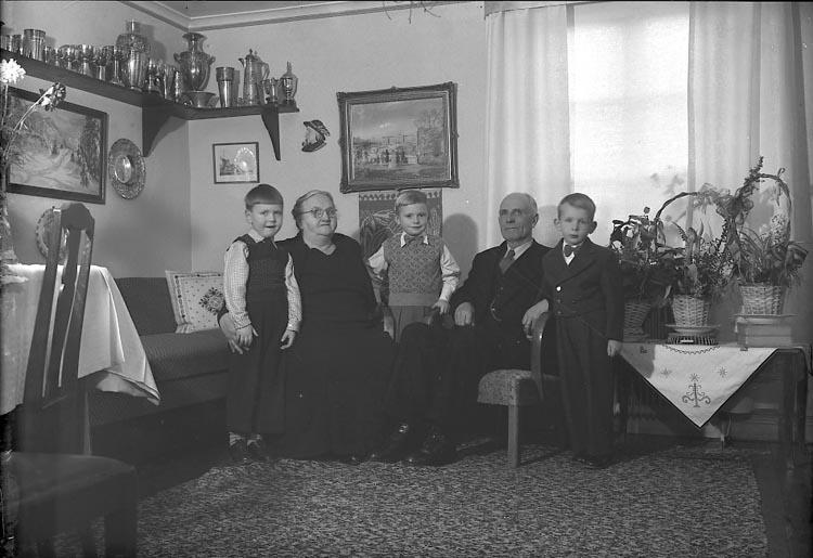 """Enligt fotografens journal nr 8 1951-1957: """"Olsson, Herr o Fru med barnbarn"""". Enligt fotografens notering: """"Herr Ernst Olsson med Fru och barnbarn Höviksnäs""""."""