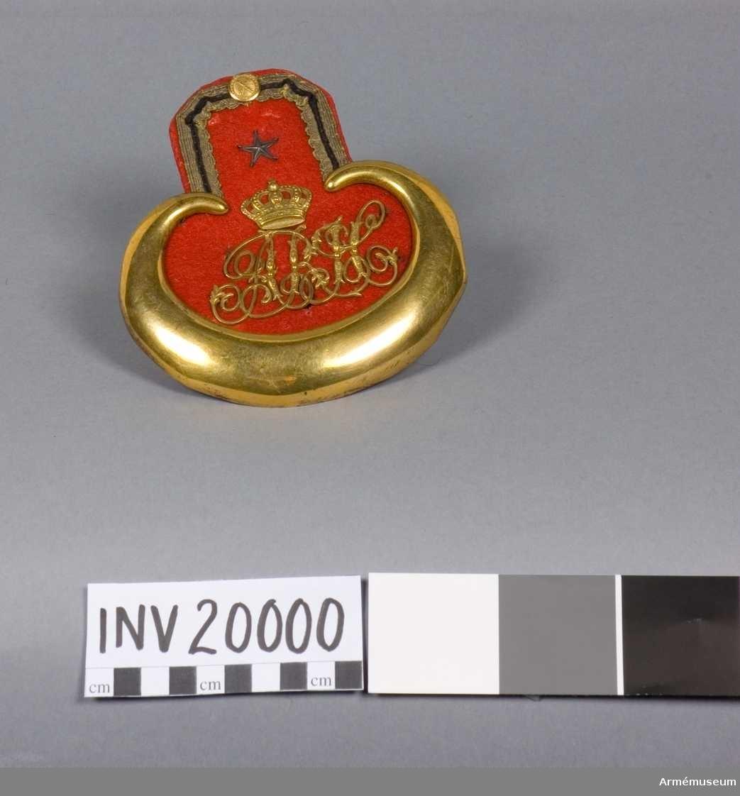 """Grupp C. Tillhörande officersuniform omkring 1830-talet. Epålett med matta av rött kläde och gul galon (med svarta snören i mitten) omkring övre delen. Omkring den nedre delen en förgylld plåt. Fodrad med rött kläde och har namnchiffer """"A.R.H-"""" med krona ovanför av gulmetall. Ovanför kronan femuddig stjärna och knapp med fältmarsalkstavar i kors (generalstabsknappar)."""