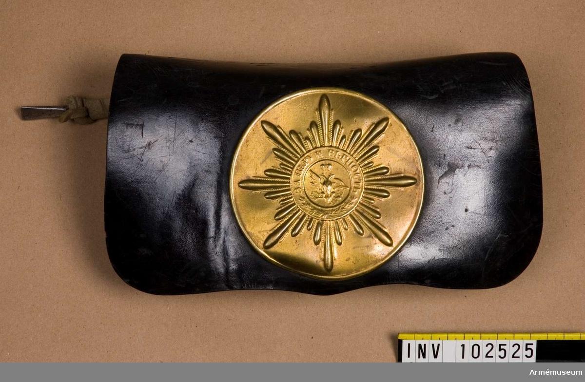 """Grupp C II. För menig av Gardets kavalleri, 1820-30-talet (m/1812). Består av två delar:  LOCK av tjockt svart läder, fastsytt vid väskan. Mitt på  locket en rund mässingsbricka med en ingraverad S:t Andreas- stjärna (beteckning på Gardets trupper). På stjärnan står Gardets paroll """"För tro och trohet"""" på ryska; se bilaga. I stjärnans mitt en dubbelörn. Brickan har på baksidan öglor, med vilka de med en smal rem fästes vid locket. På baksidan av locket en läderlapp med knapphål fastsydd för fastsättning vid lådan.   LÅDA av metall betäckt med brunt läder. På sidorna två halv- runda läderlock. På baksidan två korta remmar fastsydda, vid vilka pistolladdstocken är fäst. Lådlängd 20 cm. Lådbredd 10 cm. Bandolärrem saknas."""