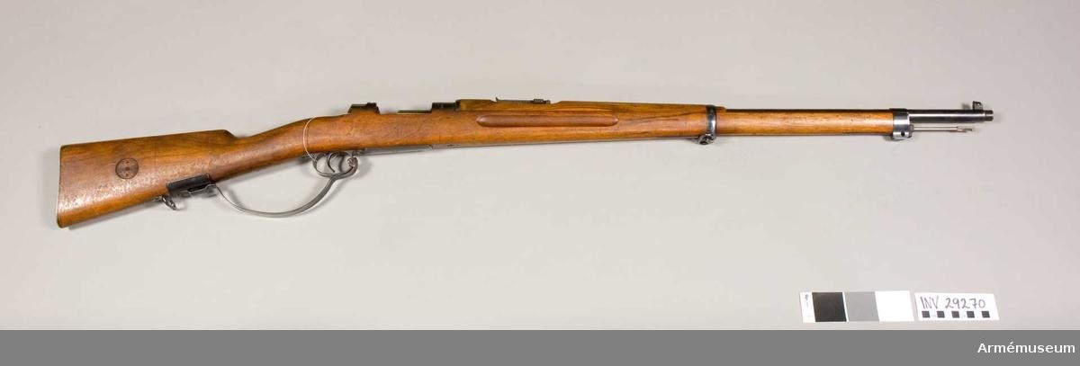 """Grupp E II f. Modellexemplar med extra """"varbygel""""  Gevärets tillverkningsnummer: 11003. Samhörande gevärsrem, vid geväret fästad fastställningslapp på vilken skriften delvis är oläslig."""