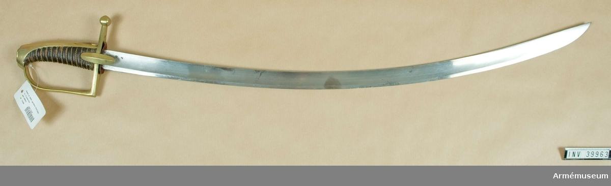 """Grupp D II Klingans bredd upptill 34 mm. Klingan är krökt, skålslipad samt till större delen av sin längd eneggad, men 22 cm ovanför udden får den egg även på ryggsidan. Udden ligger vid ryggen. Upptill på terssidan finns ett par stämplar och på ryggen står """"Mfture Imple du Klingenthal Conlaux Freres"""".  Fästets beslag är av mässing.  Kaveln är lindrigt framåtböjd samt klädd med svart skinn. Runt den går en spiralreffla 17 varv. I bottnen på denna reffla är en av två parter hopsnodd mässingstråd anbringad, vilken tråd längst ned vid parerstången är lindad tre varv omkring kaveln. Baktill har kaveln ryggbeslag, som upptill övergår i en upptill tvärt avskuren kappa. På kappan finns en låg, avlång nitknapp.   Parerstången är rak. På över och undersidan är den flat, men på sidorna har den ryggar. Baktill avslutas den av en knapp, som har fyrkantig genomskärning, dock med svagt avfasade kanter.  Från parerstångens främre ände utgår handbygeln i rät vinkel. Handbygeln blir uppåt något bredare, och har framtill längs vardera kanten en grund ränna, så att bygeln får förhöjd rygg på mitten. Handbygelns övre ände är instucken under kappans kant. Styrskenorna är rätt långa och ovala, med förhöjd rygg på mitten. På undersidan av parerstångens bakre arm är ett Y inslaget och på översidan av samma arm finns ett par otydliga stämplar med inskriften """"Versailles"""".Dylika sablar användes till 1816  Samhörande nr AM.39963-4"""