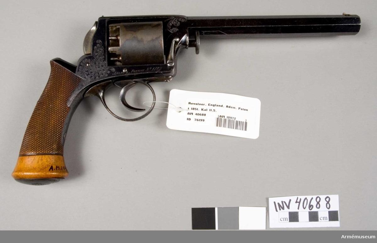 """Grupp E III. Revolver med en pipa och trumma för fem skott. Loppets rel.längd: 16 kaliber.På pipans översida står """"Manuf-d by Antoin & C-ie, Liege Licensed by Adams & Deane, London"""". På den vänstra sidan en stämpel """"Adams patent 1851"""" och på motsvarande sida """"Adams patent nr: 1127"""", vilket är tillverkningsnumret. Förvärvad genom byte år 1933."""
