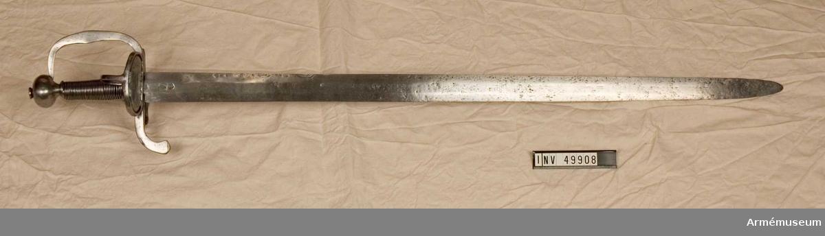 Grupp D II.  Värja enligt uppgift för infanteriet. Från 1600-talets mitt.   Klingan är tveeggad med flata åsar samt upptill på innersidan märkt med ett krönt, dubbelt C. Fästet är av järn.   Knappen är  lökformig. Upptill på knappen finns en låg, konisk nitknapp och nedtill en mycket kort, konisk hals.   Kaveln har varit lindad med metalltråd, rester sitter kvar  nedtill. Parerstången är platt, nedböjd baktill och övergår framtill i båge i handbygeln, vars övre ända är instucken i ett hål på knappen. På yttersidan finns en ganska stor, oval parerring, som varit utfylld av en nu förkommen parerplåt. På samma sida går en nedtill i två grenar kluven sidbygel från knappen till korsringen. På innersidan finns också en parerring. Den är mindre än den  förstnämnda och har parerplåten, med vilken den är utfylld, i  behåll. Från innersidans parerring går en tumbygel till kavelns  nedersta del. På yttersidan är parerstången, parerringen, ytterbygeln och handbygeln ornerade med snedställda, infilade streck. Det är möjligen tvivelaktigt, om klinga och fäste ursprungligen hört samman.