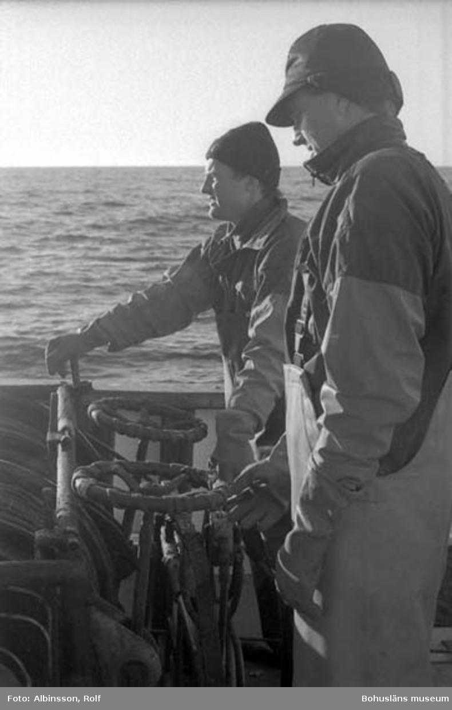 """Enligt fotografens noteringar: """"Närmast Bengt Persson och Harald Hansson. När man lättar går det till så att den som styr kör tillbaka mot trålen samtidigt som man tar in slacken i wiren.""""  Fototid: 1996-03-07."""