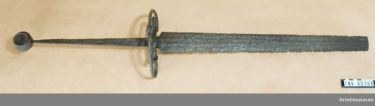 Grupp D II. Klingans bredd vid basen är 55 mm. Klingan är avbruten och mäter  nu 550 mm.Ursprungligen nordtysk typ från 1400-talets senare hälft.Knappen är rund, tämligen tjock och med plant avskuren ut- och insida, dess utsida med insänkt runt fält (sannolikt för inpassande av ornering i emalj eller ädelmetall).Den ursprungliga, raka eller böjda parerstången har i Sverige utbytts mot den nu befintliga njurformiga pareranordningen av enkelt flätat rundjärn, påminnande om en kringla. Dylikt utbyte  av pareranordningen förekom på skandinaviskt område under  1400-talets slut och 1500-talets början.Klingan är jämnt avsmalnande mot udden och med tre grunda blodränder. Något mer än en tredjedel avbruten