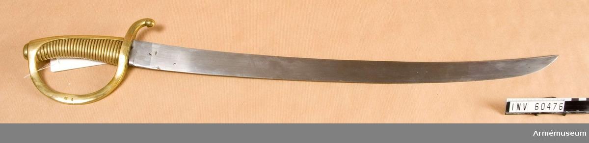 Grupp D II.  Klingans bredd upptill är 36 mm. Pilhöjden är 20,5 mm. Klingan är krökt och eneggad med kilformigt tvärsnitt.  Fästet är helt av mässing och gjutet i ett stycke. Kaveln är svagt framåtböjd.  Baktill på kaveln är ett ryggbeslag, som uppåt övergår i en på översidan tvärt avskuren kappa, markerad.  På kappan finns en stor oval, avrundad nitknapp. Kaveln har 27 horisontala räfflor.  Parerstången har fyrkantigt tvärsnitt, dock på kvarts- och terssidan något kullrig.  Baktill är den nedböjd och slutar i en avrundad knapp, men framtill övergår den  i båge i handbygeln. Den sistnämnda har samma sorts tvärsnitt som parerstången och är upptill förenad med kappan.