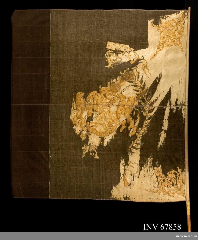 """Duk: Tillverkad av enkel, vit taft, sydd av två horisontella våder.   Dekor: Målad omvänt lika på båda sidor: i mitten svenska riksvapnet under pfalziska huset i guldkonturer. Skölden kröns av stor, sluten kunglig krona och hålls av två dubbelsvansade guldlejon. Runt vapnet en krans av två lagerkvistar i guld med omväxlande gröna blad och grönskaftade guldbär, upptill och nedtill ihopknuten med lika rosetter av guld.  Över kransen, på ett av guldkonturer bildat inskriptionsband, fragment av guldtext. I hörnen ornament i guld.  Fanduken fäst vid stången med gult sidenband och förgyllda spikar.  Stång av furu, avsmalnande nedtill.  Märkt på stången, spikad lapp med påskrift: """"No 1079"""" och """"Karl XI:s"""" (Lenk)."""