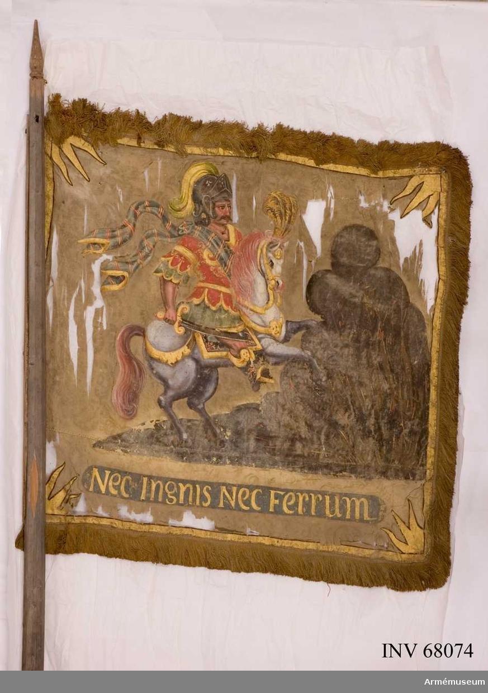 Duk: Enkel(?), tillverkad av beigegul damast med horisontell skarv. Duken fäst vid stången med en överlagd träslana, islagen med järnbultar.  Dekor: Målad lika på båda sidor, ryttare i rustning som påminner om den romerska, harnesk i guld och rött över grön guldkantad klädnad; skarf i grönt med ränder i rött och guld med fladdrande ändar; på huvudet hjälm med uppslaget visir och gyllene grönskiftande hjälmbuske; på fötterna mörka (romerska?) stövlar med röda ornament och gyllene kant; förande ett orientaliskt svärd med guldfäste.  Den vita hästen galopperar på mörk mark in i en stor rykande eld med orange flammor; hästens man och svans i rött, mundering i guld och gul (guld?) plym i pannan; sadelkåpan mörk med röda ornament och guldkant.  I nedre delen ett språkband med guldbokstäver på mörk grund och längs kanten guldram med svart kant, från vilken i hörnen inåtgående tredelade flammor.  Frans: Dubbel, av gult och brunt (rött?) silke.  Stång: Tillverkad av trä, facetterad, mörkmålad, defekt nedtill.