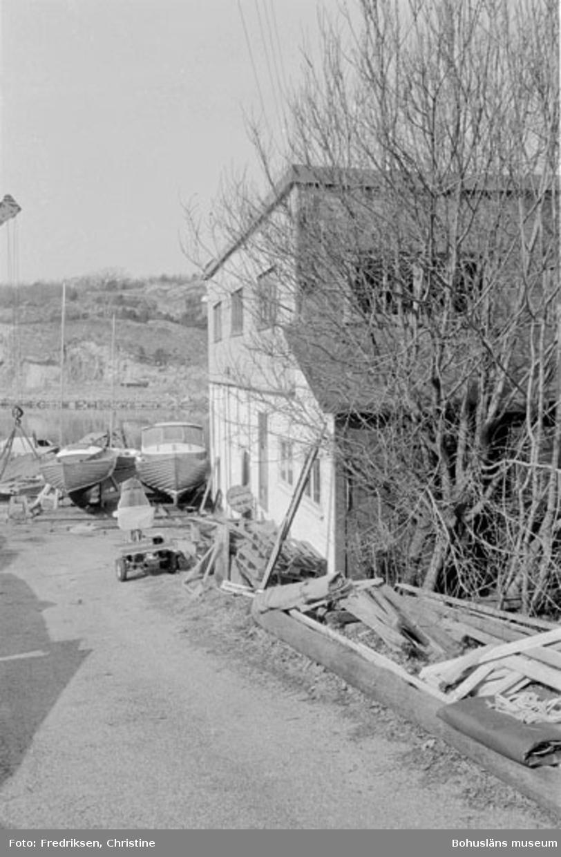 """Motivbeskrivning: """"Nilssons Båtbyggeri, Bojarkilen, Strömstad. Verkstadsbyggnaden."""" Datum: """"19800429."""" Riktning: V."""