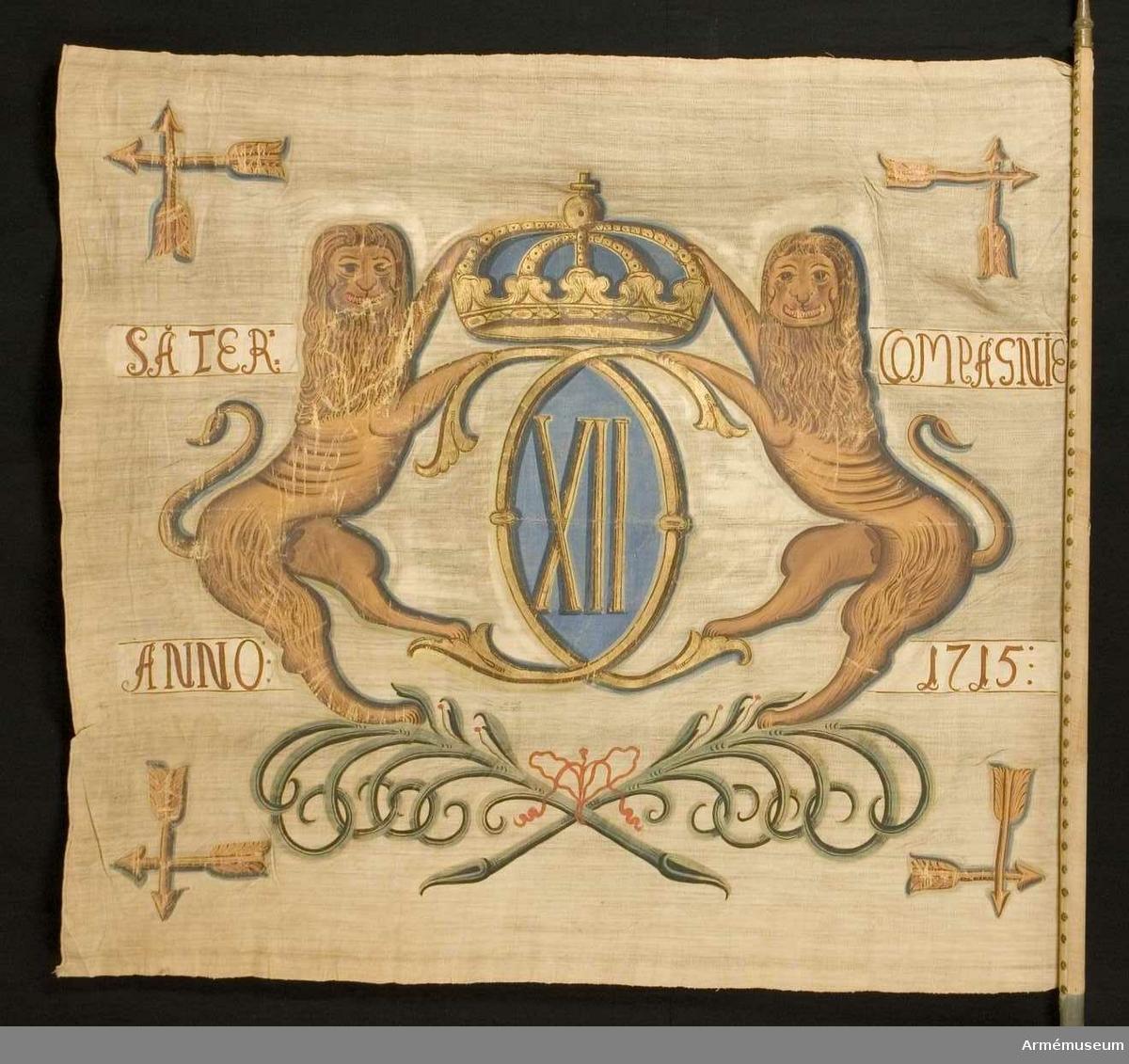 Duk: Tillverkad av enkel vit linnelärft. Två våder horisontellt sammankastade, med kastfållen åt insidan. Vertikala kantfållen lagd åt utsidan. Duken är fäst med en strumpa fastsydd runt stången, och därpå med mässingstennlickor på ett band. Bandet fortsätter ned på stången.  Dekor: Målad lika på båda sidor, texten på utsidan i brunt och på insidan i svart. Karl XII:s namnchiffer, dubbelt C inom vilket XII, under sluten krona, allt i guld. Chiffret är uppburet av två gulbruna lejon, som står på två korsade och med en mycket liten rosett i rött hopbundna palmkvistar (lagerkvistar?) i grönt med mycket små röda bär i svart. I hörnen två korslagda dalpilar. Text skriven på ömse sidor om chiffret, utanför lejonen i gult.  Stång: Tillverkad av trä och blåmålad.