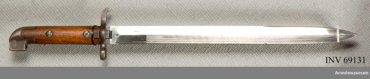 Tveeggad klinga av stål med dito fäste. Fästet är försett med plattor av trä. Saknar tillverkningsnummer.