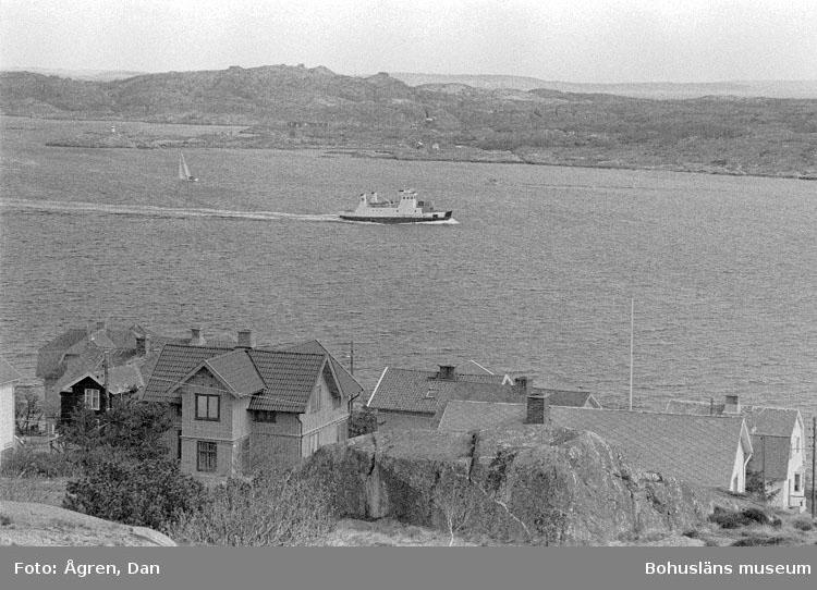 """Motivbeskrivning: """"Bebyggelse på Hälsö, nordöfärjan och Björkö i bakgrunden mot Ö."""" Datum: 19800502"""