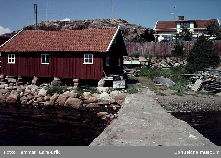 """Motivbeskrivning: """"F.d varv i Skredsvik, Bottnafjorden. Varvet drevs av båtbyggare Johan Jonasson fram till år 1942 och av Karl Johansson 1942-1975. På bilden syns till vänster bostadshuset, till höger båtbyggarverkstaden."""" Datum: Juli 1980."""