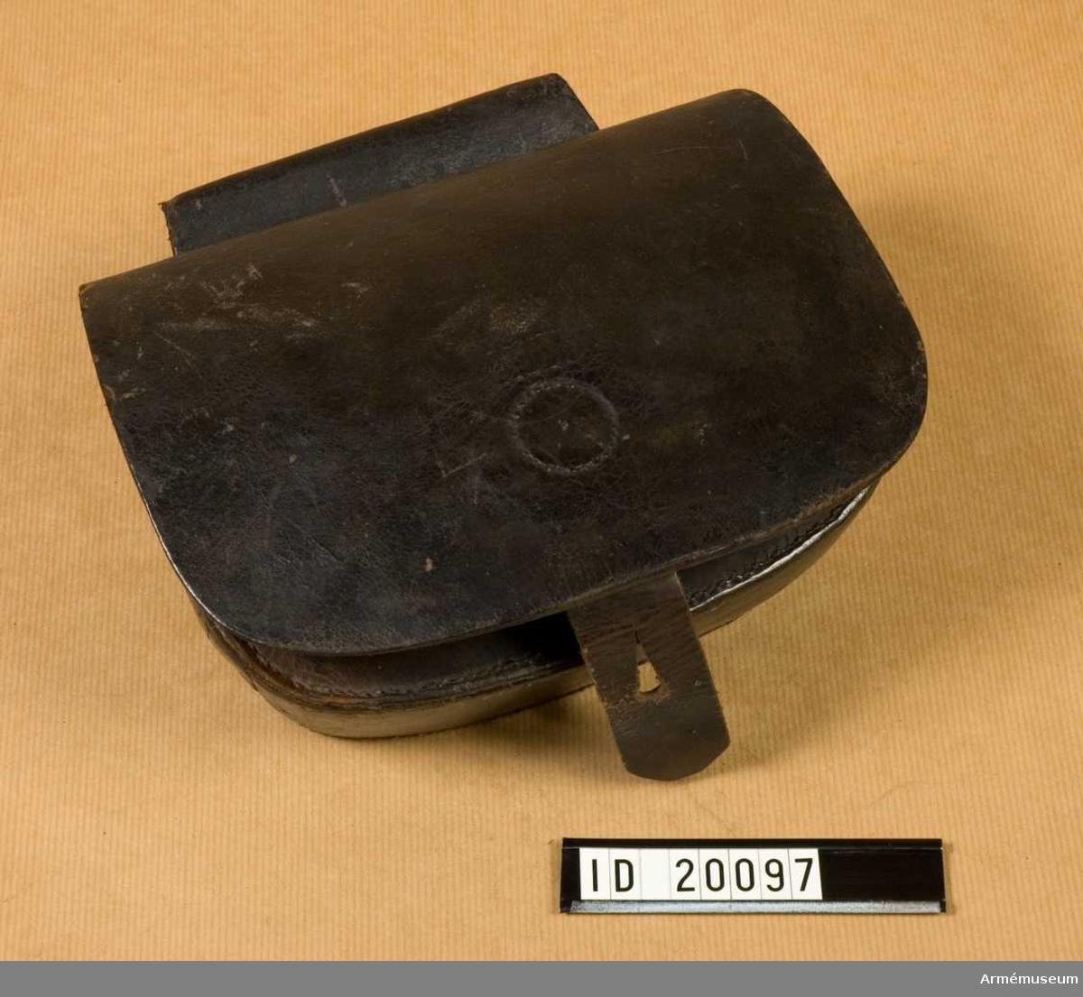 """Grupp C:II. Reparationsmodell  Av svartlackerat läder. """"Ink. på auktion vid Axevall af gifvaren"""". G. av major Carl Broman 24/10 1881. Pl.n. 122 F.w."""