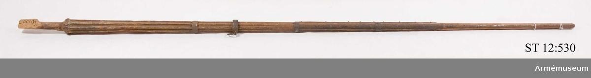 Löst fragment av linne med rostiga hål från tännlikorna. Fäst i linnestrumpan är bitar av gul sidendamast.