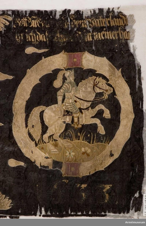 Inre och yttre sidorna spegelvänt lika: Rustningsklädd man till häst galopperande på blomsteräng, omgiven av lagerkrans. Upp- och nedtill sammanhållen av band. I dukens hörn änglahuvuden med två vingar. Över duken strödda , horisontalt strödda flammor.