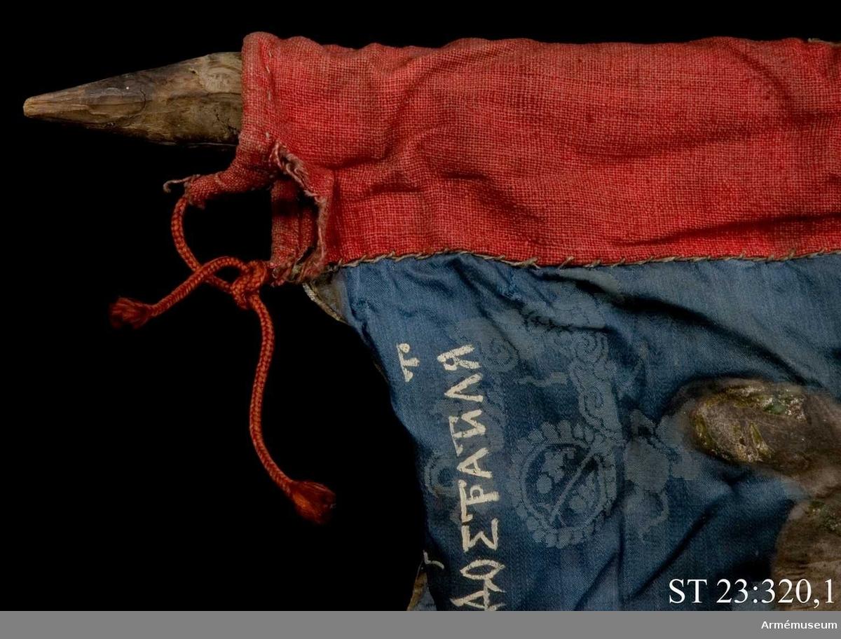 Entungad lansfana. Duk av blå kinesisk sidendamast med målad dekor. I 1703 års inventarium anges motivet vara St Göran men enligt den ryska inskriptionen är det Feodor Stratilat . Rosor och stjärnor av silver. Duken kantad med en silverbård. Strumpa av rött linne.